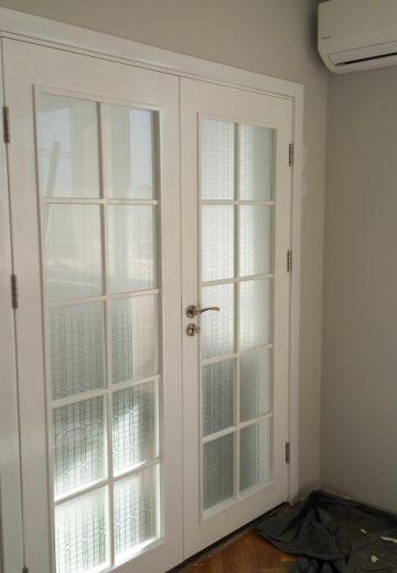 Бяла портална врата с две отваряеми крила, всяко с решетка за остъкление.