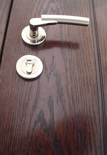 Близък план на ключалка и дръжка на входна врата на апартамент