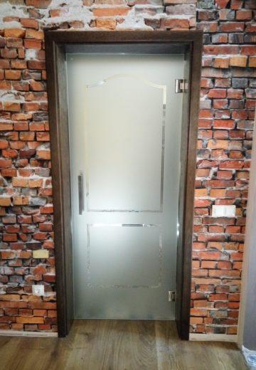 Стъклена интериорна врата с матирано стъкло, кафява каса и тапет с шарка на тухли