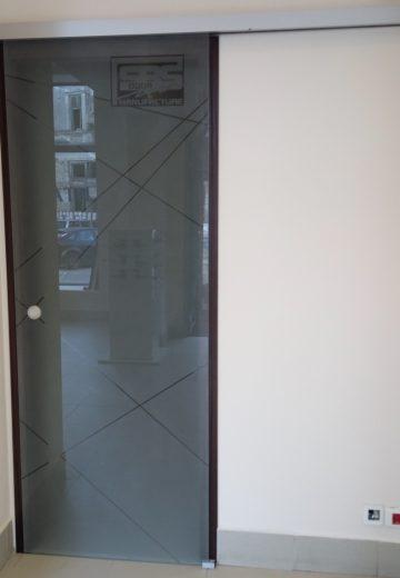 Рекламна стъклена интериорна врата с лого на SBS Design в горния десен ъгъл на матираното стъкло