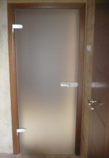 Стъклена интериорна врата с изчистено матирано стъкло, сребърни панти и дръжка, и светло-кафява каса и первази