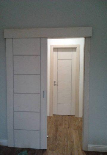Отворена еднокрила плъзгаща врата за стая с видима стандартна интериорна врата насреща.