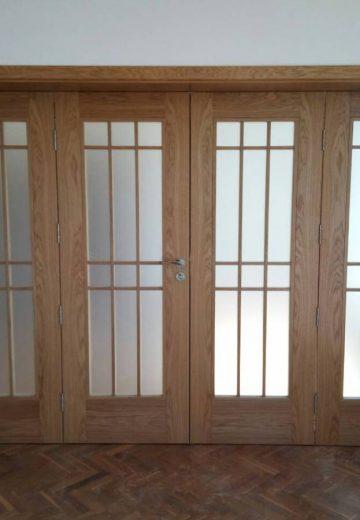 Светлокафява портална врата с решетка за остъкление в средата на всяко от четирите крила. И четирите крила са подвижни.