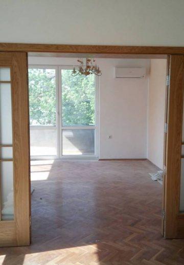 Светлокафява портална врата с решетка за остъкление в средата на всяко от четирите крила. Всички крила са подвижни, а 2 са отворени.