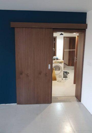 Отворена плъзгаща врата за стая, монтирана на синя стена.