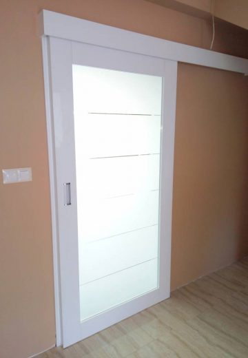 Затворена бяла плъзгаща врата от MDF и декоративно стъкло.