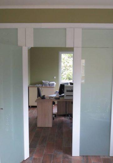 Четирикрила интериорна портална врата за офис, изработена от боядисан MDF и стъкло. Вратата има надстройка. Едно от двете подвижни крила е отворено.
