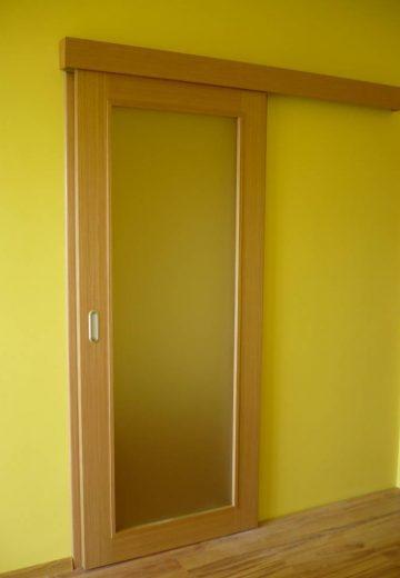 Затворена еднокрила плъзгаща врата за хол. Плъзгащата врата е с остъкление и горно водено, монтирана на жълта стена.