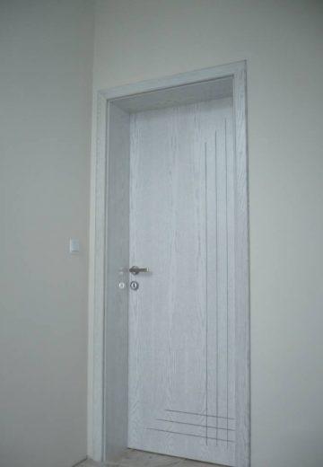 Плътна интериорна врата, изработена от естествен фурнир. Вратата има фрезовани линии, които се пресичат в долния десен ъгъл на вратата (снимка от дясната страна)