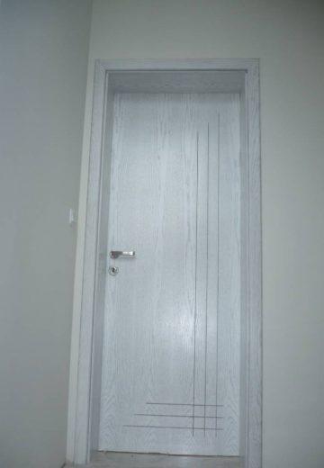 Плътна интериорна врата, изработена от естествен фурнир. Вратата има фрезовани линии, които се пресичат в долния десен ъгъл на вратата (снимка от отпред)