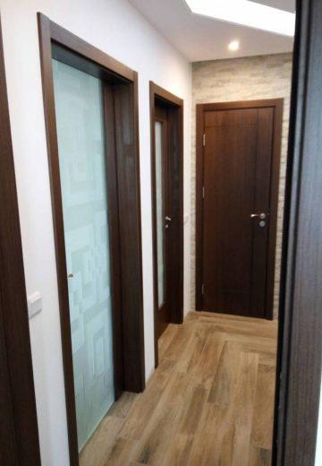 Вътрешни врати в коридор - едната врата изработена изцяло от декоративно стъкло, другата от MDF с декоративно остъкление, а вратата в дъното на коридора - от плътен MDF с естествен фурнир.
