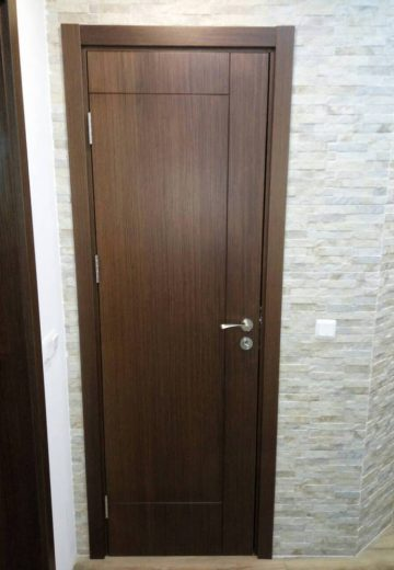 Интериорна врата от MDF - естествен фурнир, поставена на декоративна стена, имитираща камък.