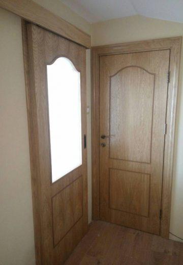 Снимка на коридор с две врати - една плъзгаща врата от MDF с остъкление и стандартна интериорна врата