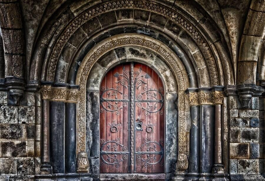 Двукрила старинна входна врата с метални елементи.