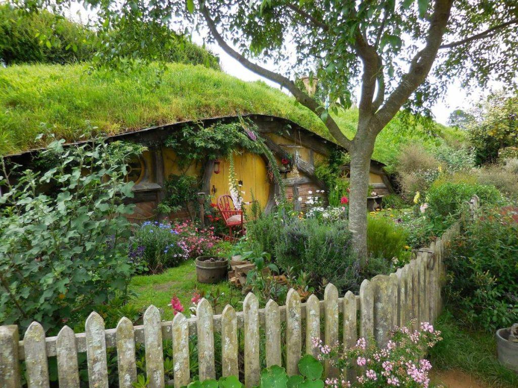 Къща в хълма с кръгла, жълта входна врата.