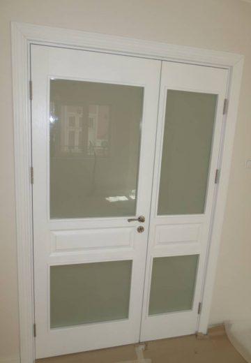 Бяла портална врата с две подвижни крила. Крилата на порталната врата са с по две стъкла в горната и долната си част.
