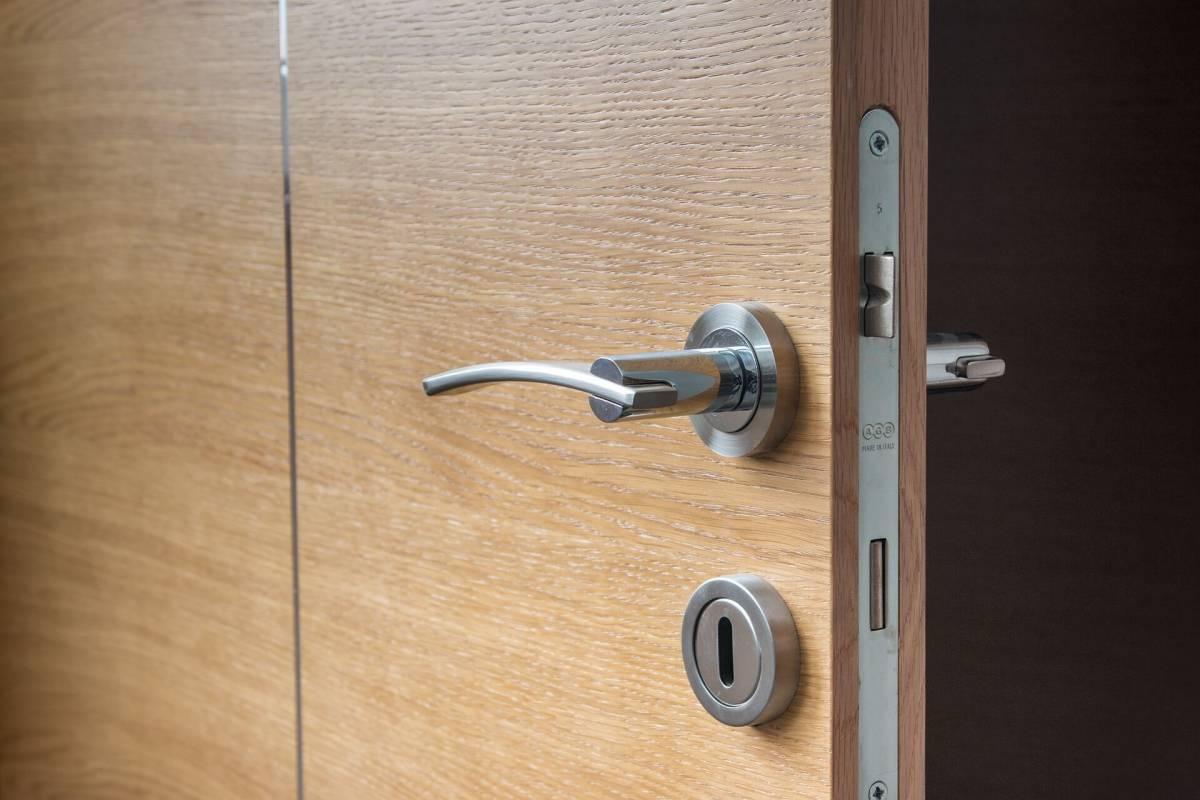 Брава и ключалка на кяфява фурнирована врата снимана в близък кадър;