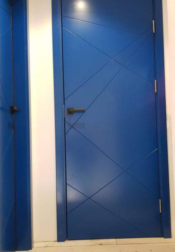 Снимка на синя интериорна врата от боядисан в синьо MDF. Вратата е плътна, с фрезовани преплитащи се линии по повърхността си и черна дръжка с прваоъгълни форми.