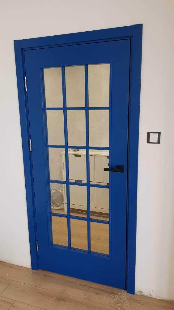 Снимка на интериорна врата от боядисан в синьо MDF. Вратата има прозорец с прозоречна решетка и черна дръжка с правоъгълни форми.