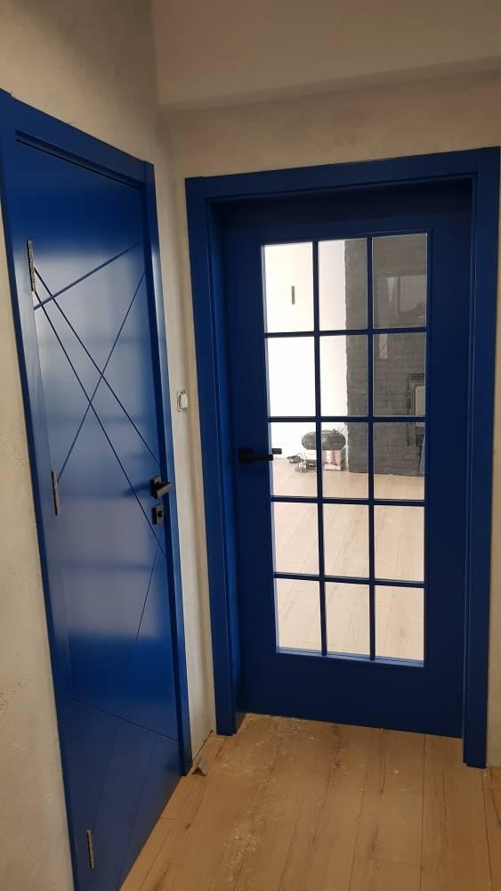 Вътрешни врати от боядисан в синьо MDF. Една от вратите е плътна, с фрезовани пресичащи се линии на повърхността, а другата вътрешна врата е направена с прозорец и прозоречна решетка.
