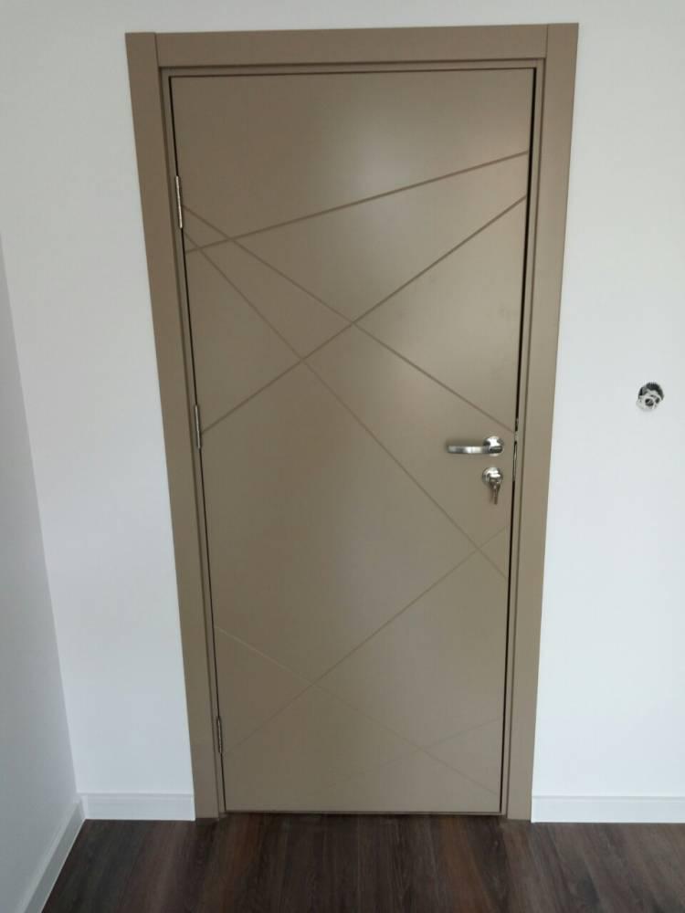 Интериорна врата от боядисан в бежово MDF. Вратата има няколко пресичащи се линии, фрезовани на повърхността ѝ. На ключалката на вратата виси ключ.
