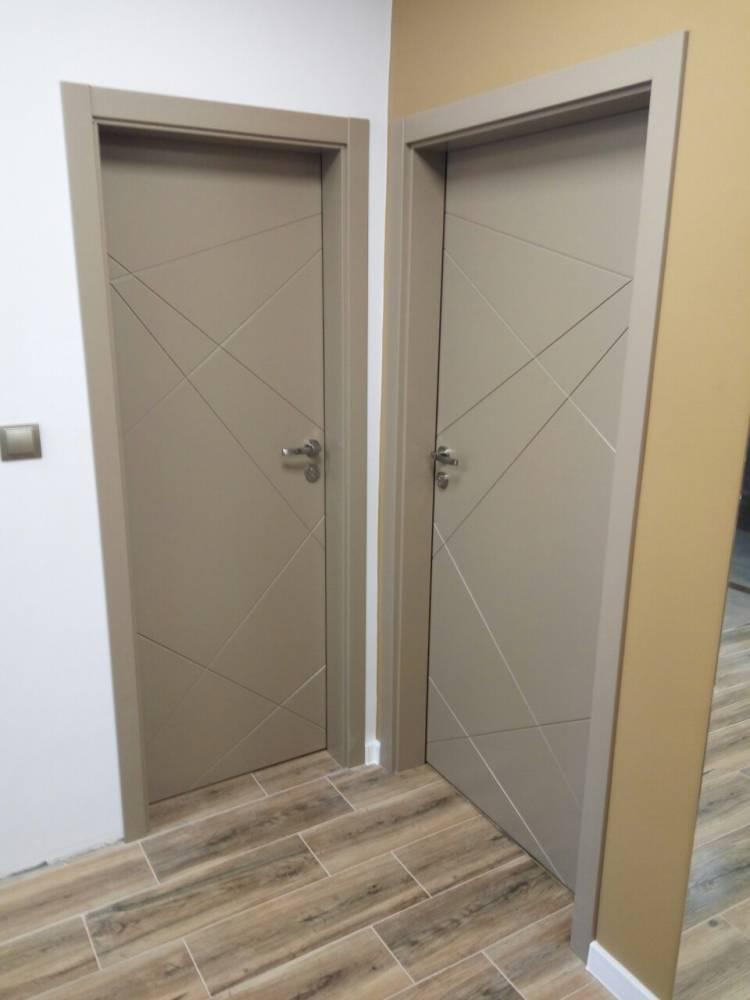 Снимка на коридор с две интериорни врати от двете страни на ъгъла. И двете врати се отварят навън и са изработени от боядисан в бежово MDF.