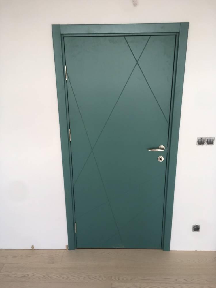 Снимка на интериорна врата от боядисан в тъмно-зелено MDF. Вътрешната врата има няколко фрезовани линии на повърхността си.