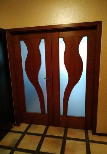 Кафява портална врата от MDF. И двете крила са еднакви на широчина и със симетрични натурални форми на остъклението.