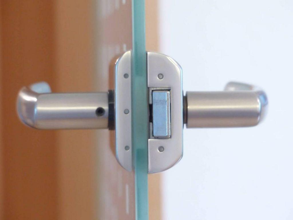 Близък план на брава и дръжка, монтирани на стъклена врата