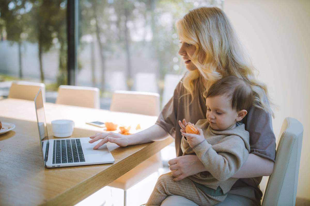 Майка с бебе в скута, която седи на кухненска маса и работи на лаптоп.